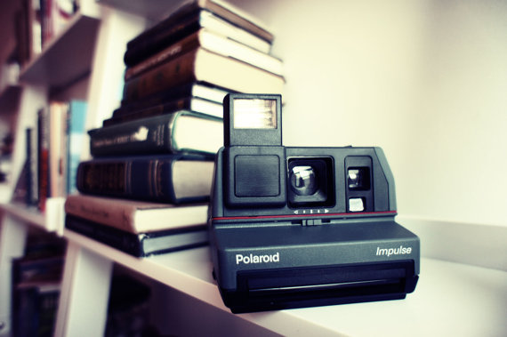 poloroid camera by a stack of books
